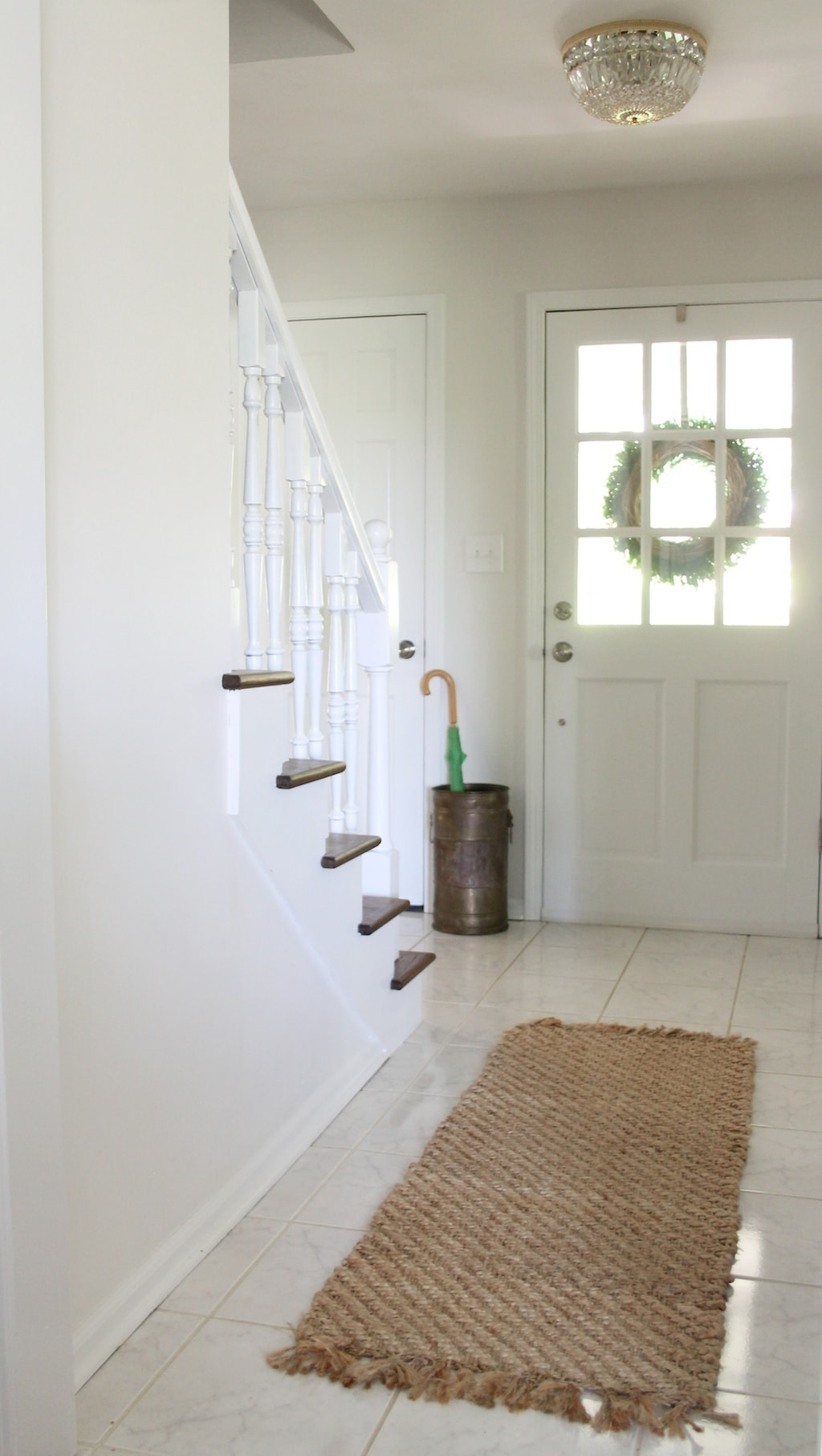 A white entry with a front door with window panes to add light to a room.