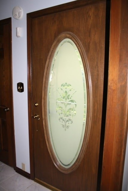 A dark and dated wood door with oval glass in an older home.