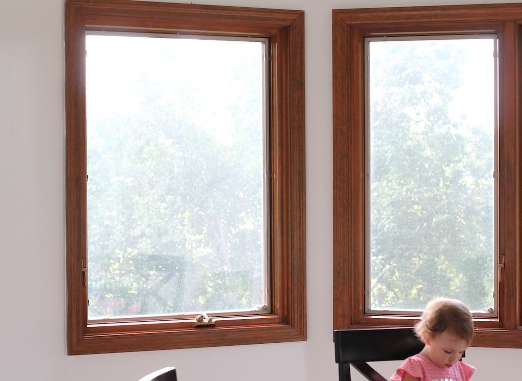 Wood windows with a little girl eating breakfast at the table in a dining room.
