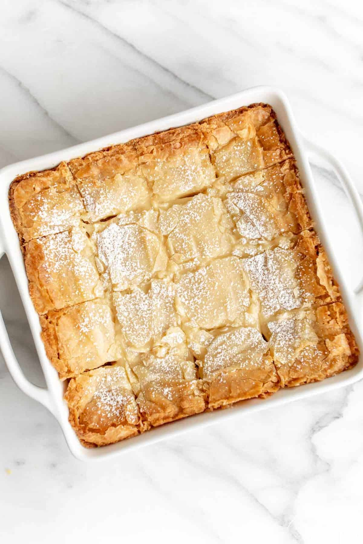 brown butter gooey butter cake garnished with powdered sugar