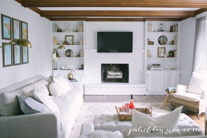 Traditional living room with wood beams, white painted brick fireplace & built-in bookcases