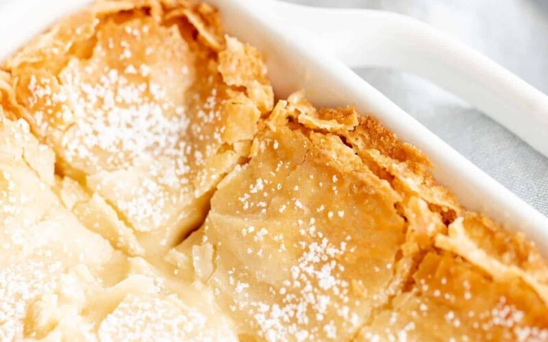 golden gooey butter cake with brown butter in white baking dish