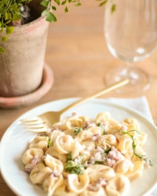 tortellacci with prosciutto arugula and truffle oil on a plate with a gold fork and glass nearby