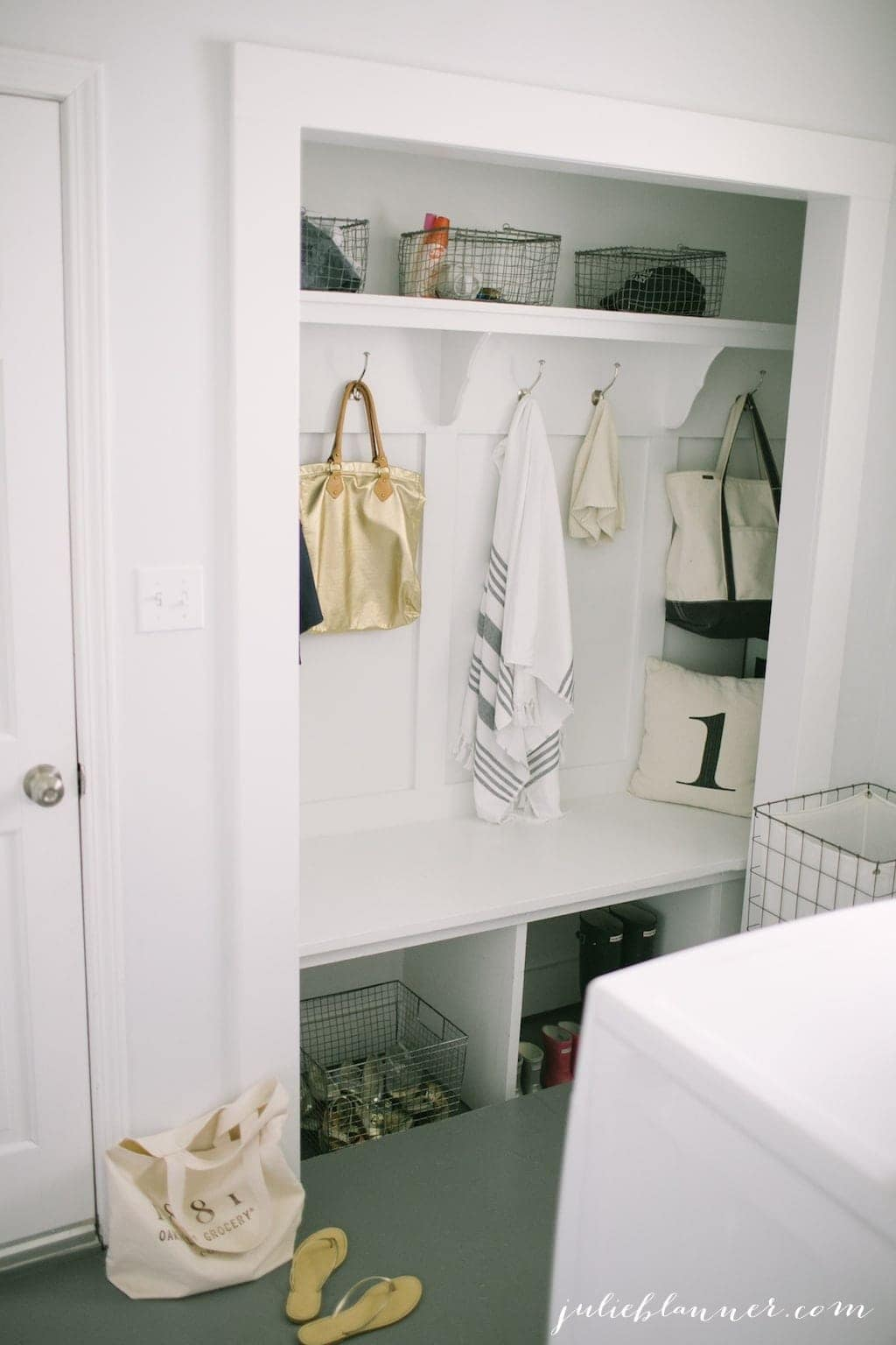 A traditional mudroom laundry room combo with unique storage solutions