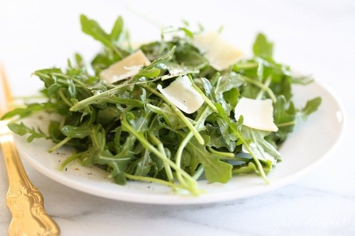 An arugula salad on a white plate, gold fork to the side.