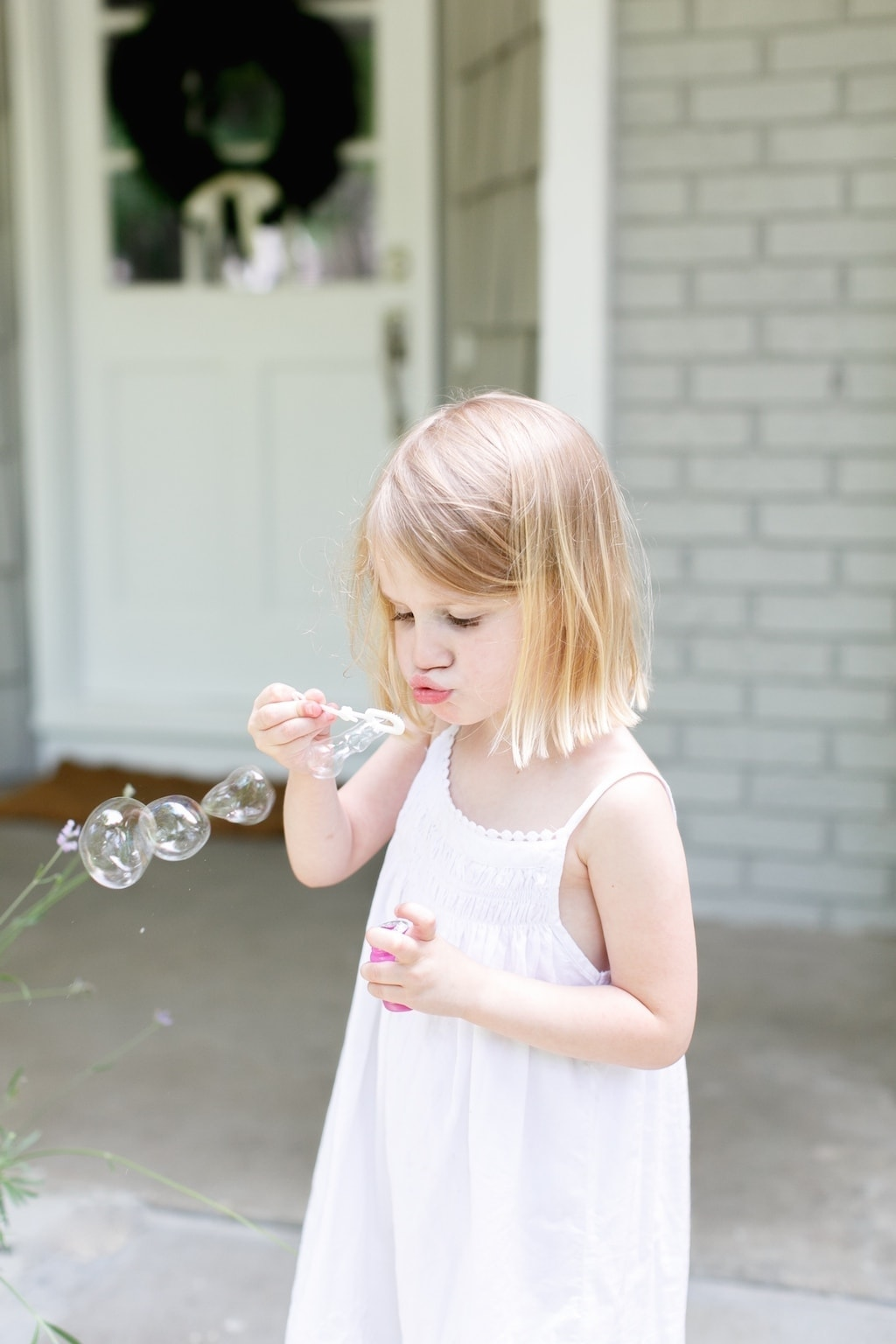 A little girl playing with bubbles
