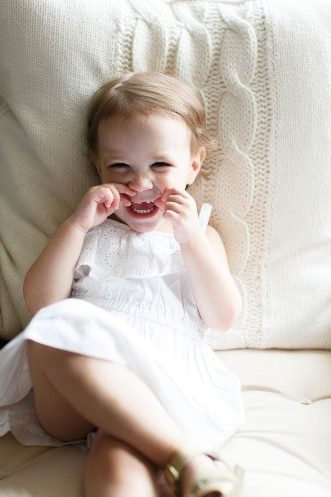 A little girl sitting on a bed