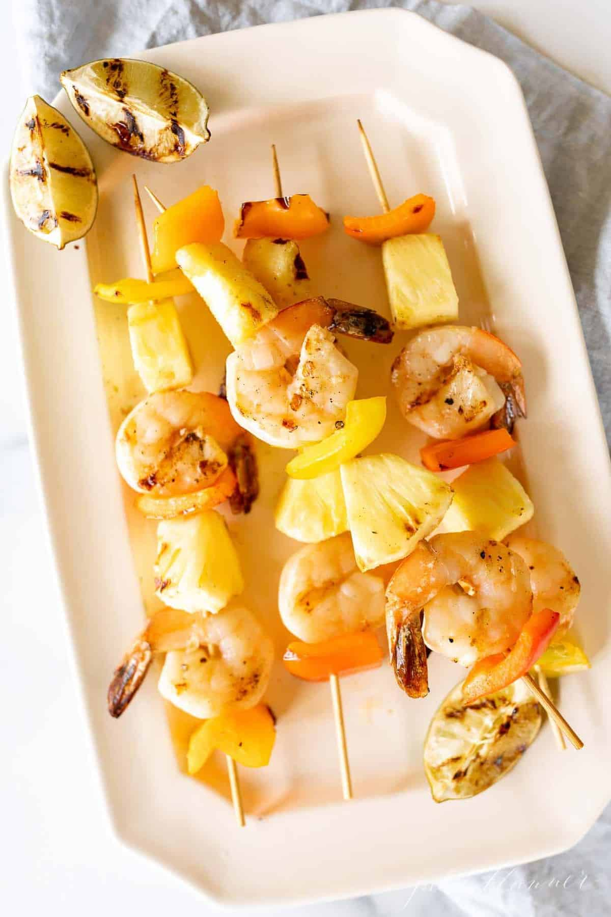 A white platter filled with shrimp kabobs for labor day menu planning.