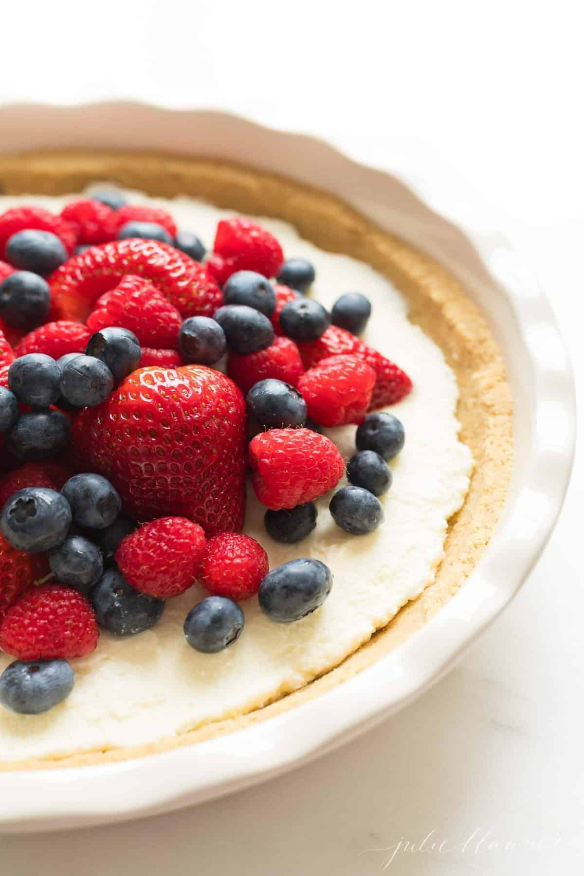 A white pie plate with a no bake lemon pie topped with berries.