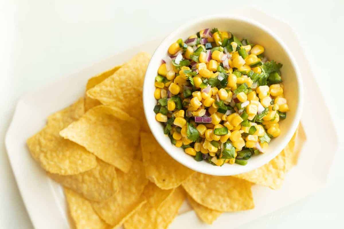 A white platter with corn tortilla chips and a bowl of corn salsa.