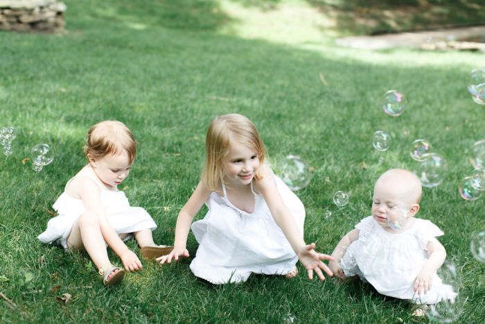 Three little girls playing with bubbles