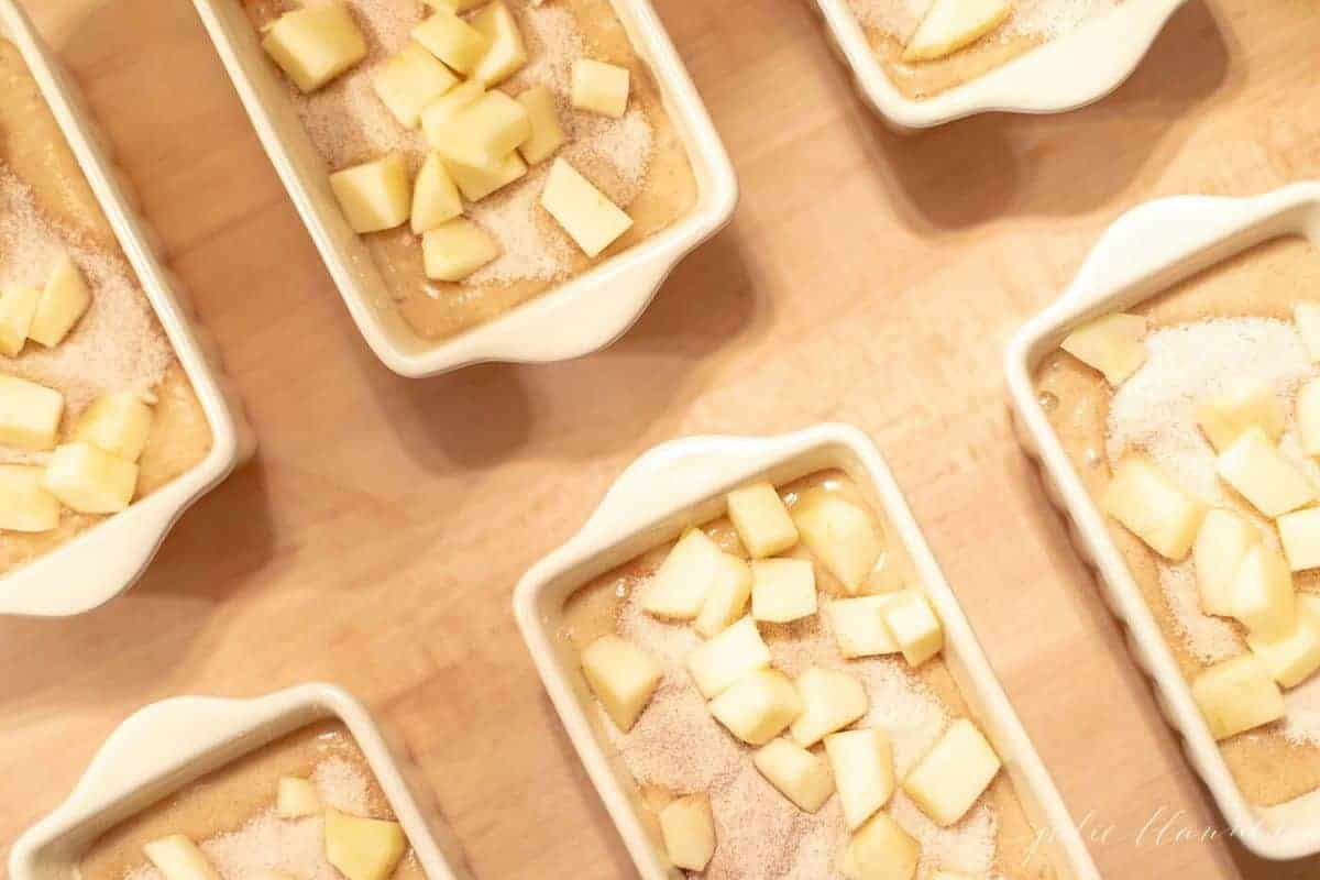 Small white ceramic loaf pans filled with apple cinnamon quick bread batter. #applequickbread