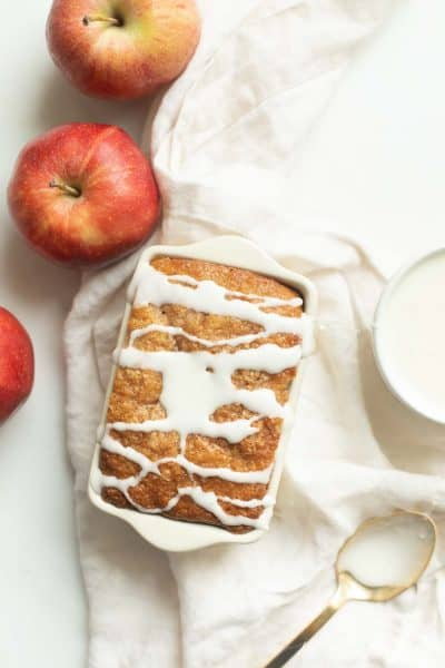 Miniature white ceramic loaf of apple quick bread, drizzled in glaze. Apples, bowl of icing and spoon rest to the side. #applecinnamonbread