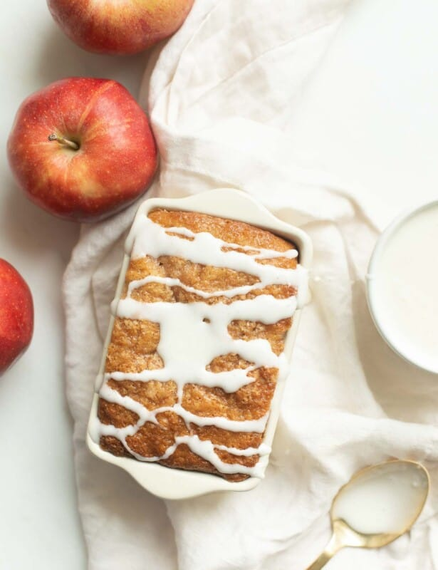A small loaf pan of apple bread, topped with white icing and surrounded with apples and a linen napkin.