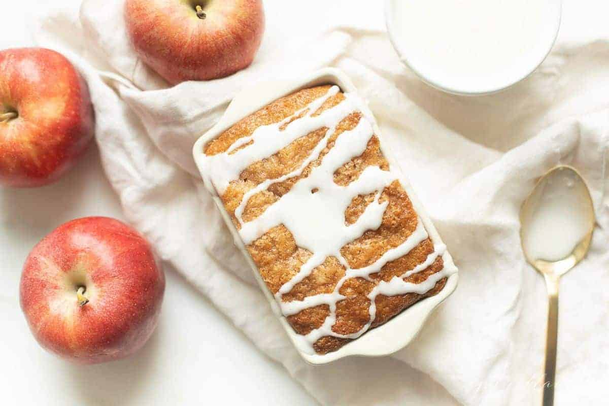White ceramic loaf pan on a white fabric backdrop, filled with quick bread and drizzled with glaze.