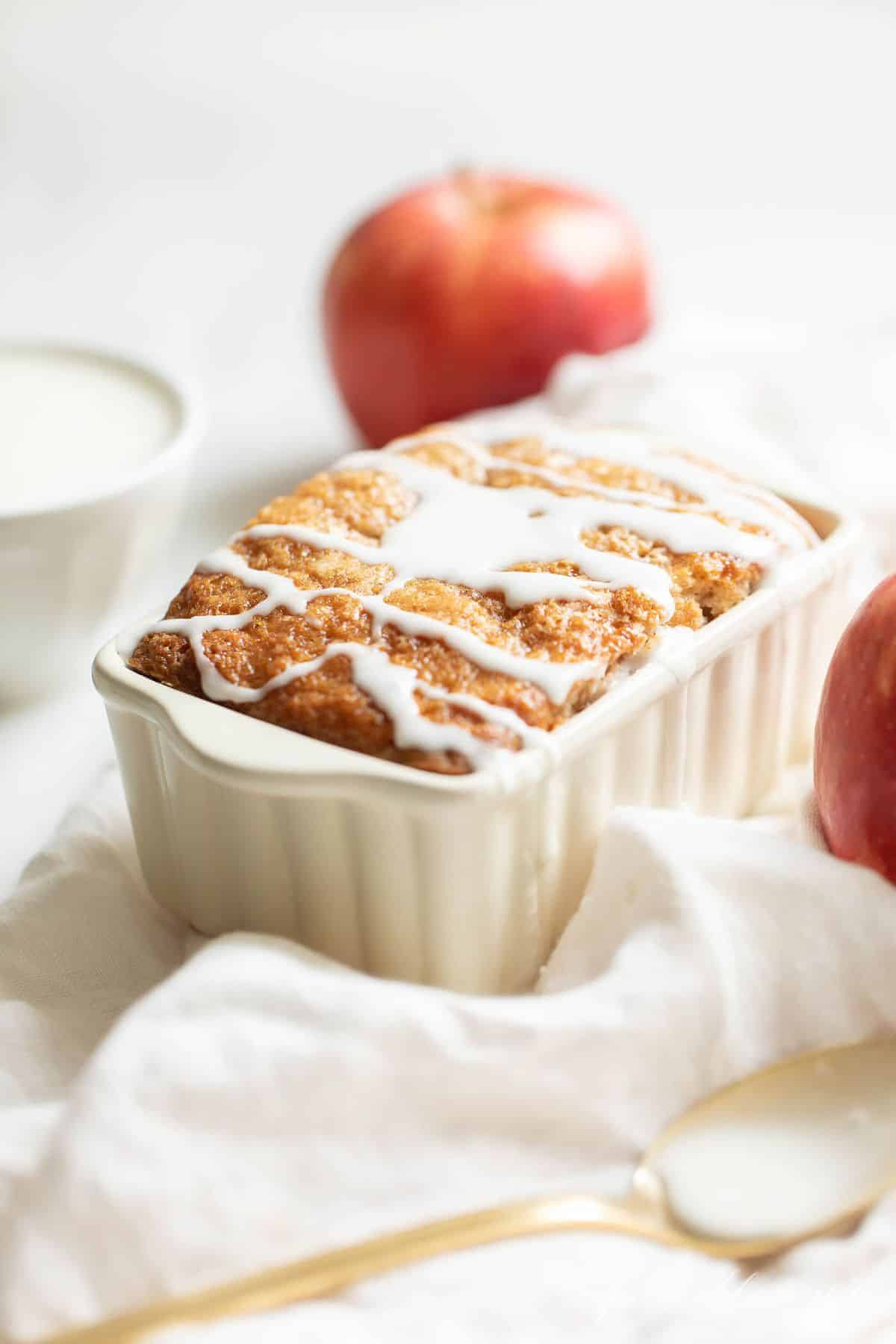 White ceramic loaf pan on a white fabric backdrop, filled with quick bread and drizzled with glaze. #applecinnamonbread #applebread #applecinnamonloaf