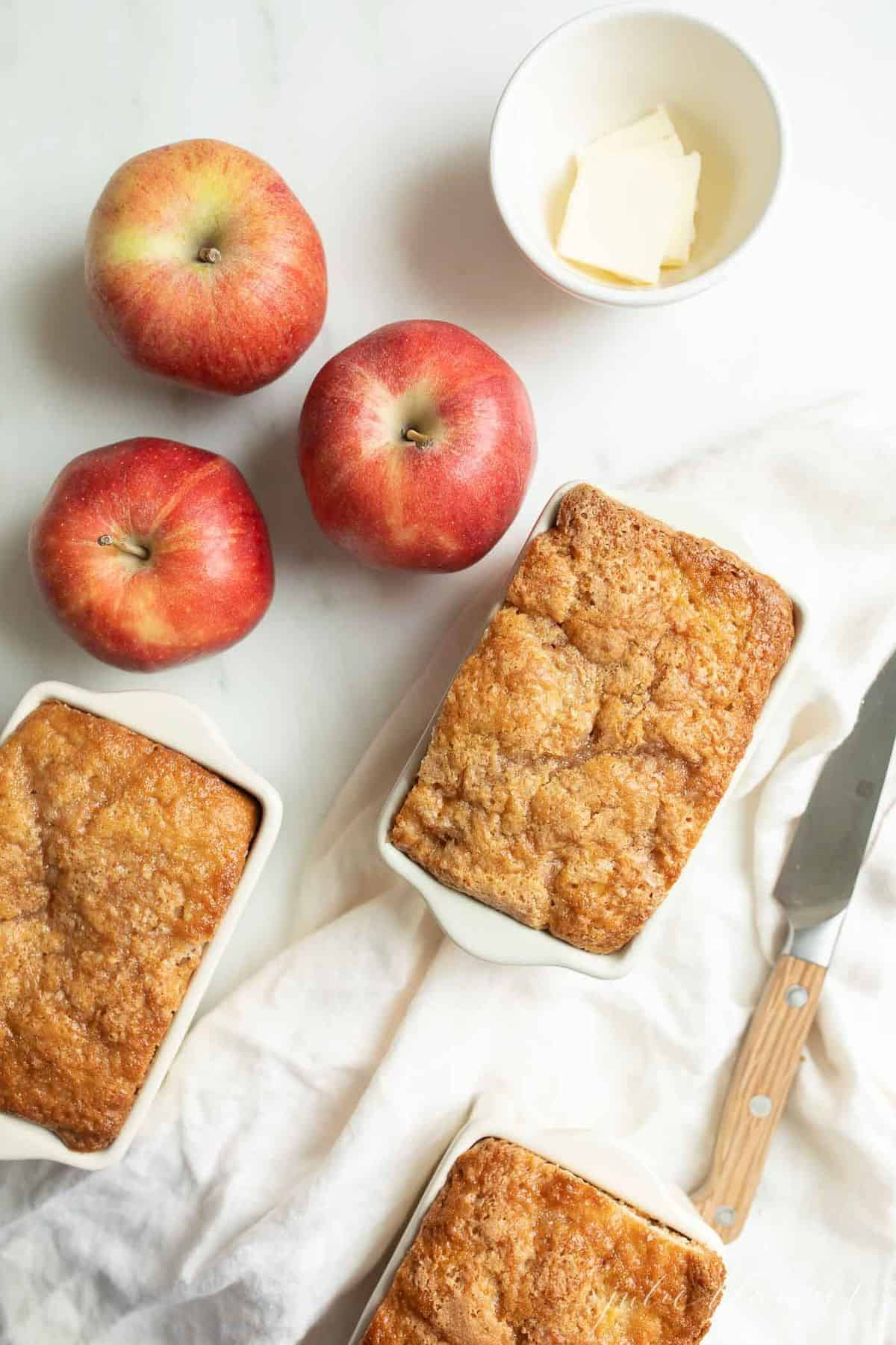 White surface with a few apples and miniature loaves of apple cinnamon quick bread.