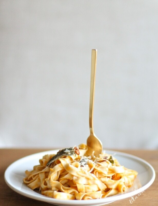 butternut squash pasta on white plate with fork sticking up