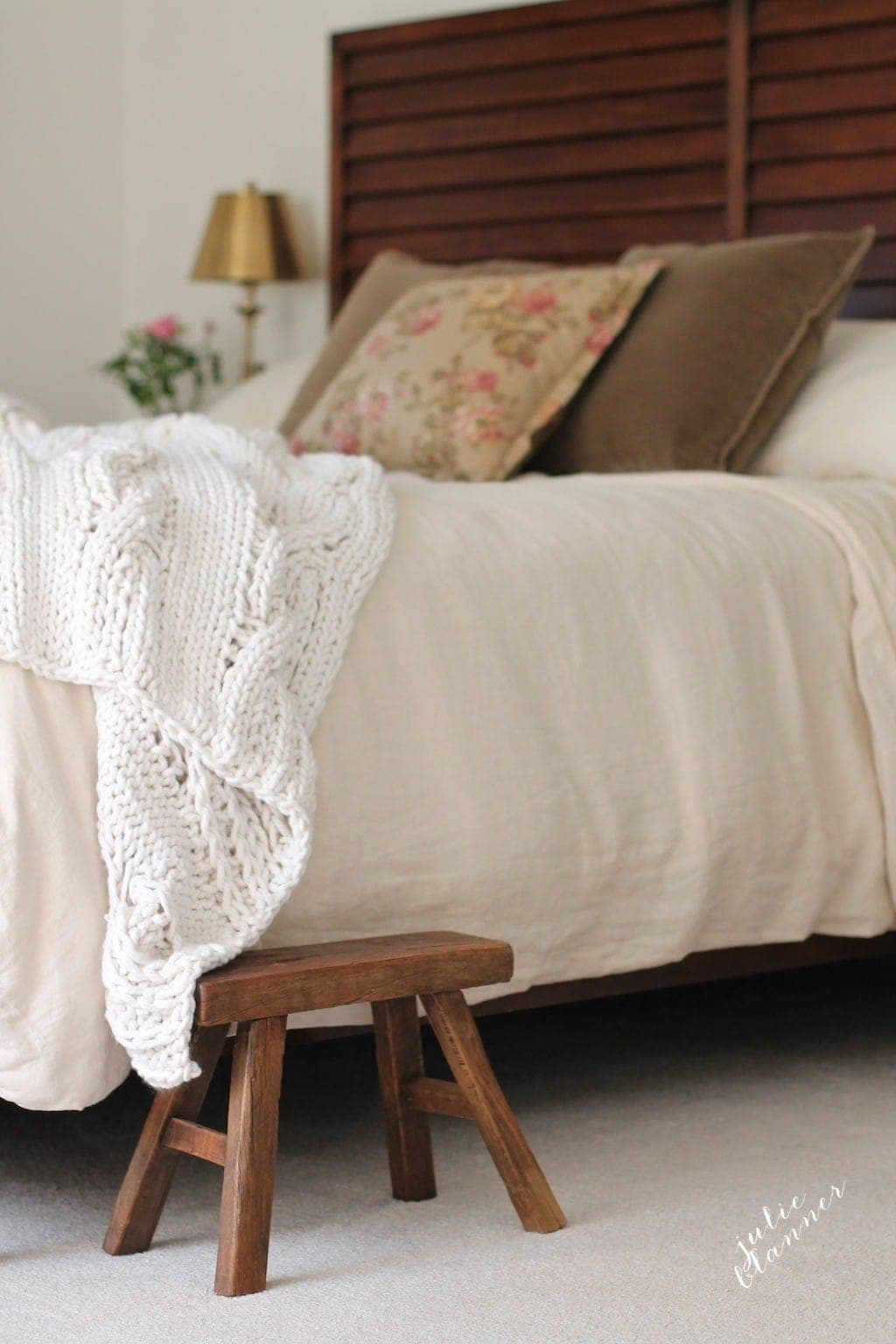 Neutral bedroom with a chunky throw, wood stool & linen duvet