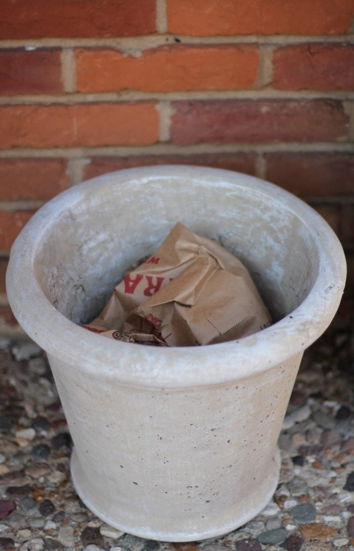 Planter with crumpled paper bag at the bottom forms the base of the outdoor winter arrangement