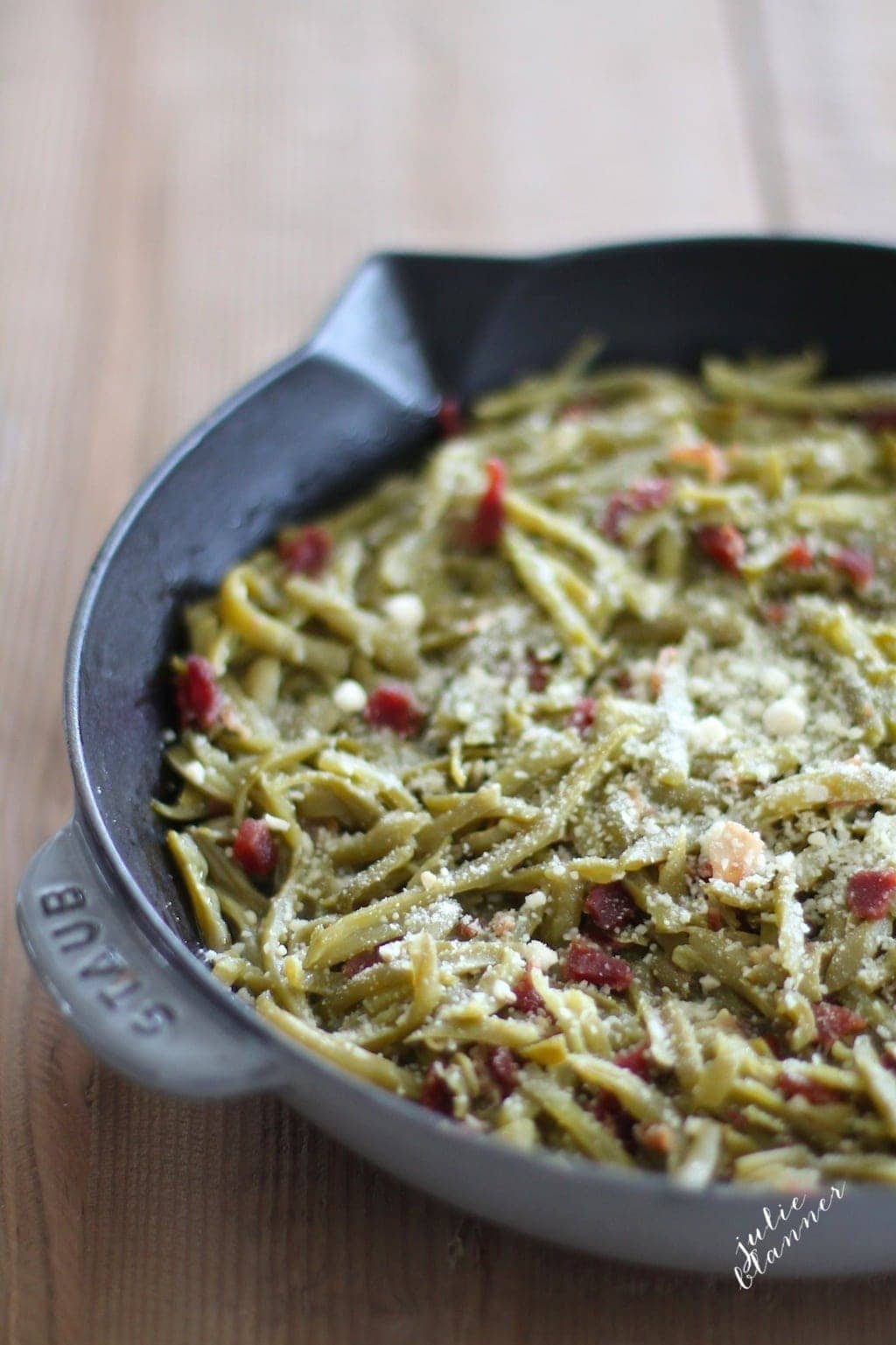 Easy green beans with bacon topped with parmesan in a skillet