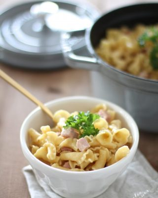 truffle mac and cheese in a white bowl with gold spoon