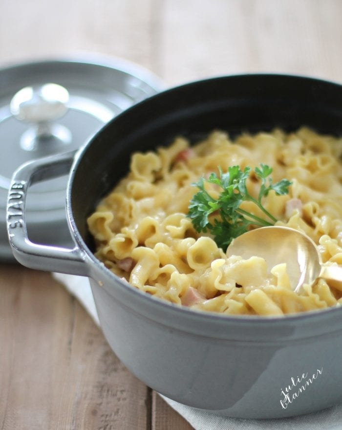 baked smoked gouda mac and cheese in a gray dutch oven with gold serving spoon