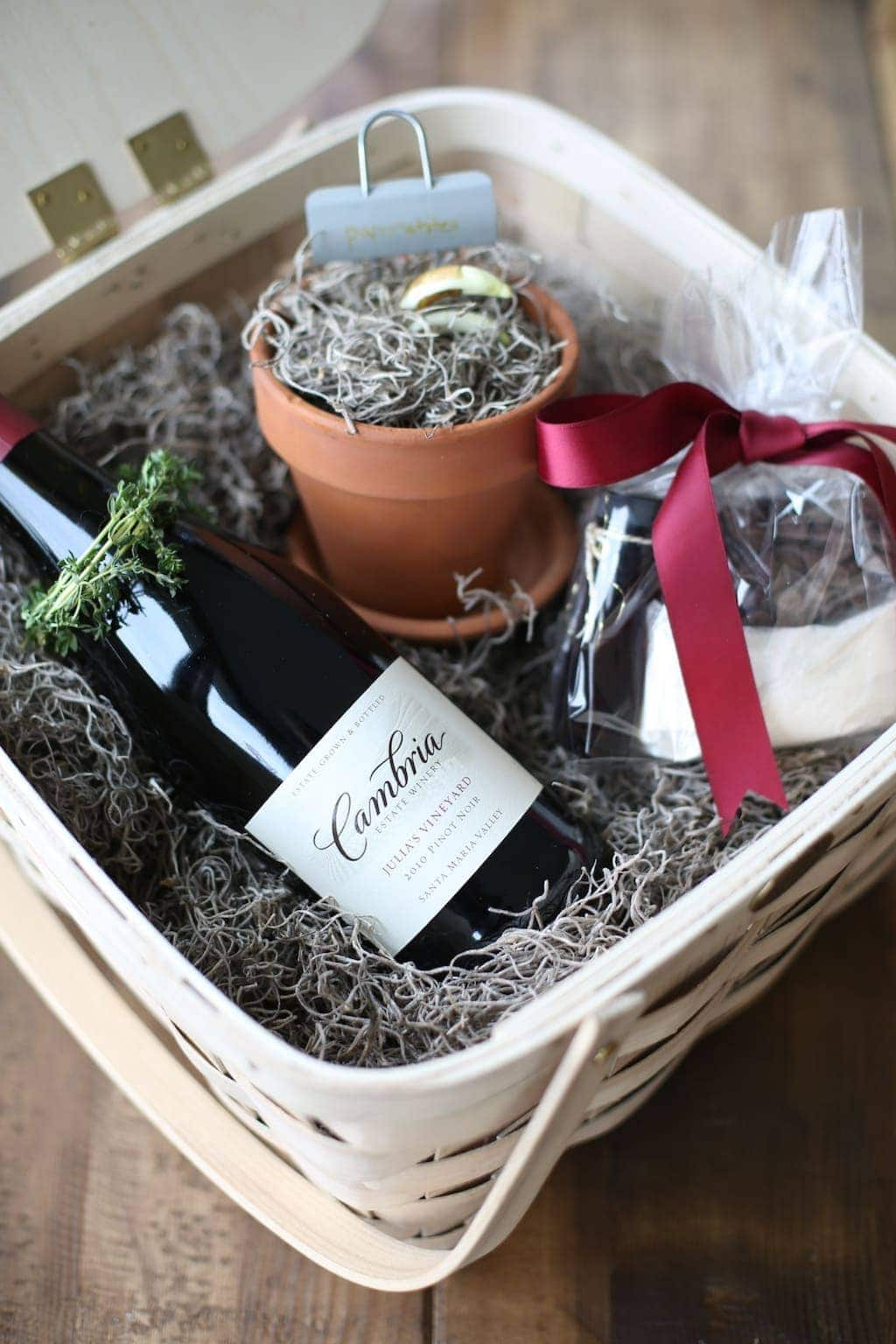 A wine and chocolate gift basket with a potted plant in the basket too.
