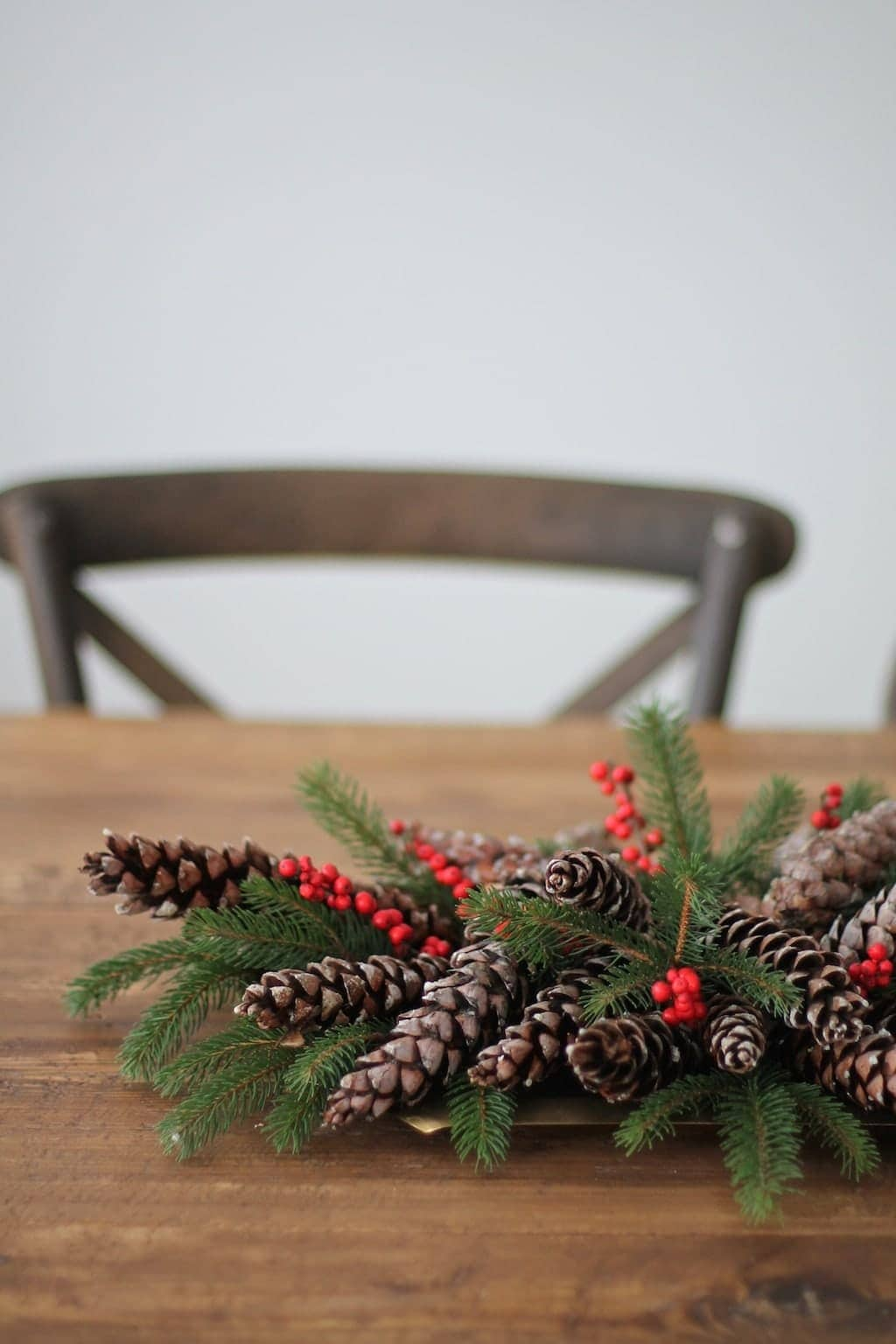 A farm table with a greenery, berry and pinecone centerpiece.