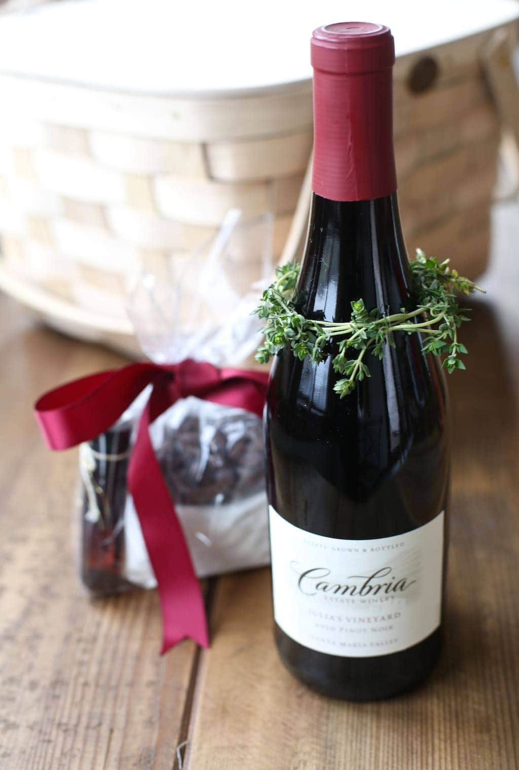 DIY herb wreath wrapped around the neck of a bottle of wine in a wine and chocolate gift basket.