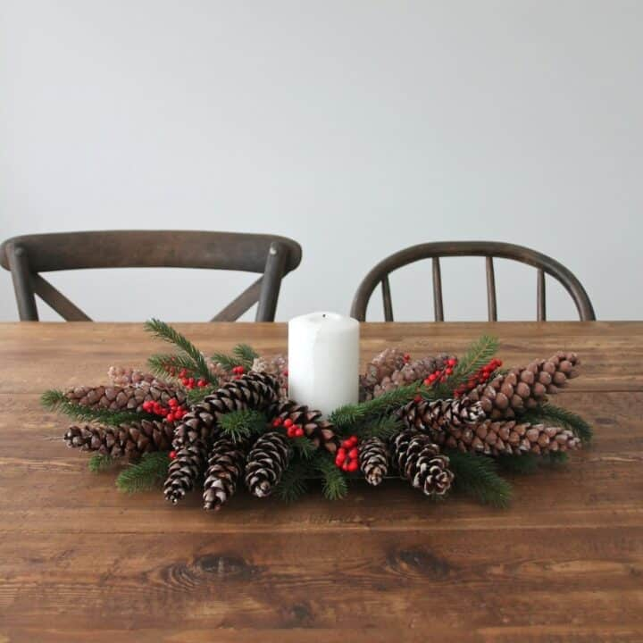 A berry and pinecone centerpiece with a candle in the middle on a farm table.