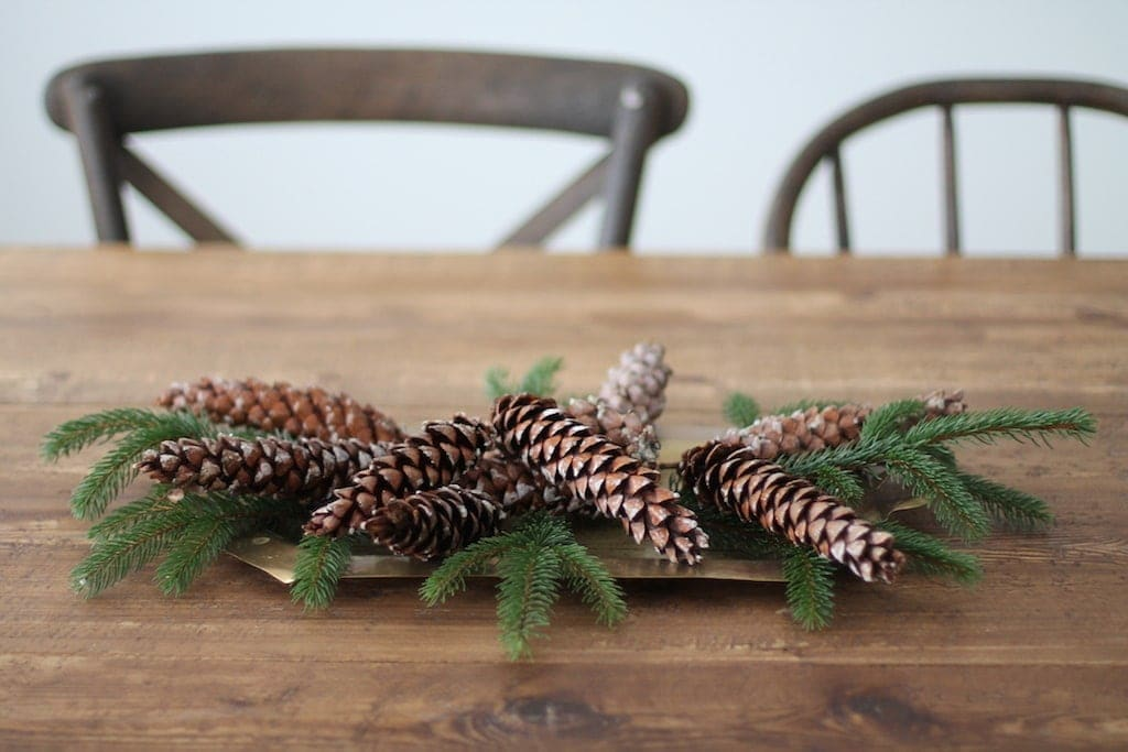 Pinecone centerpiece mixed with greenery on a farm table.