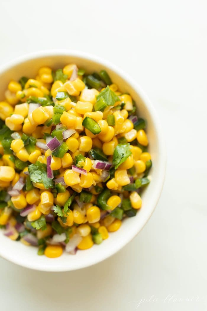 close up of corn salsa in a bowl bowl on a white countertop