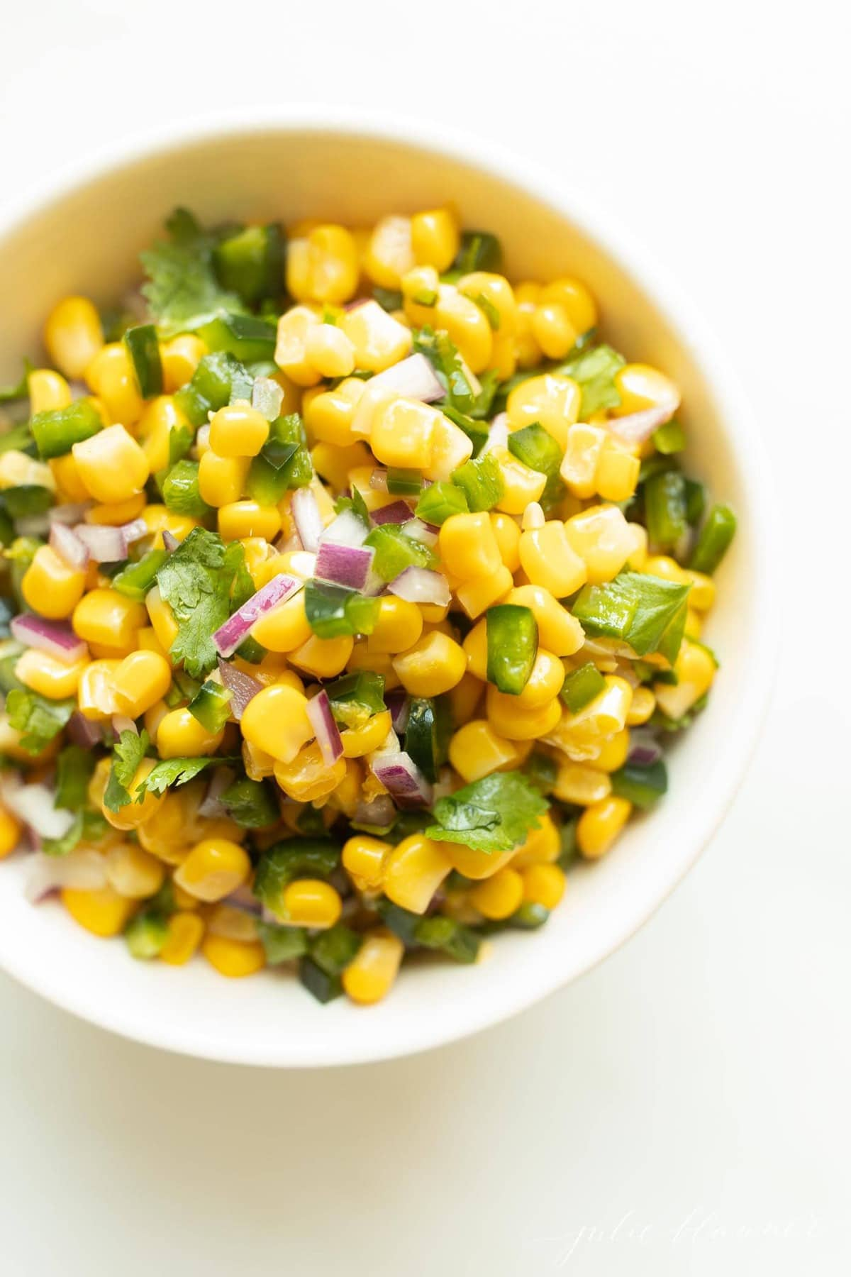 corn salsa in a white bowl with cilantro and onion
