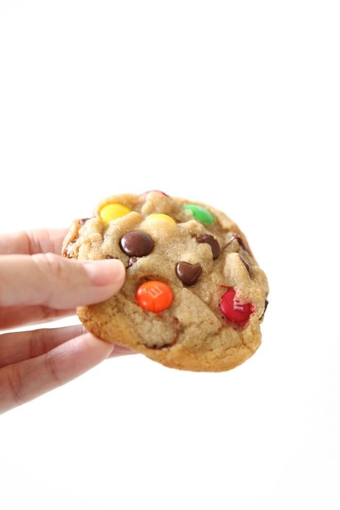 M&M cookies being held in a person\'s hand.