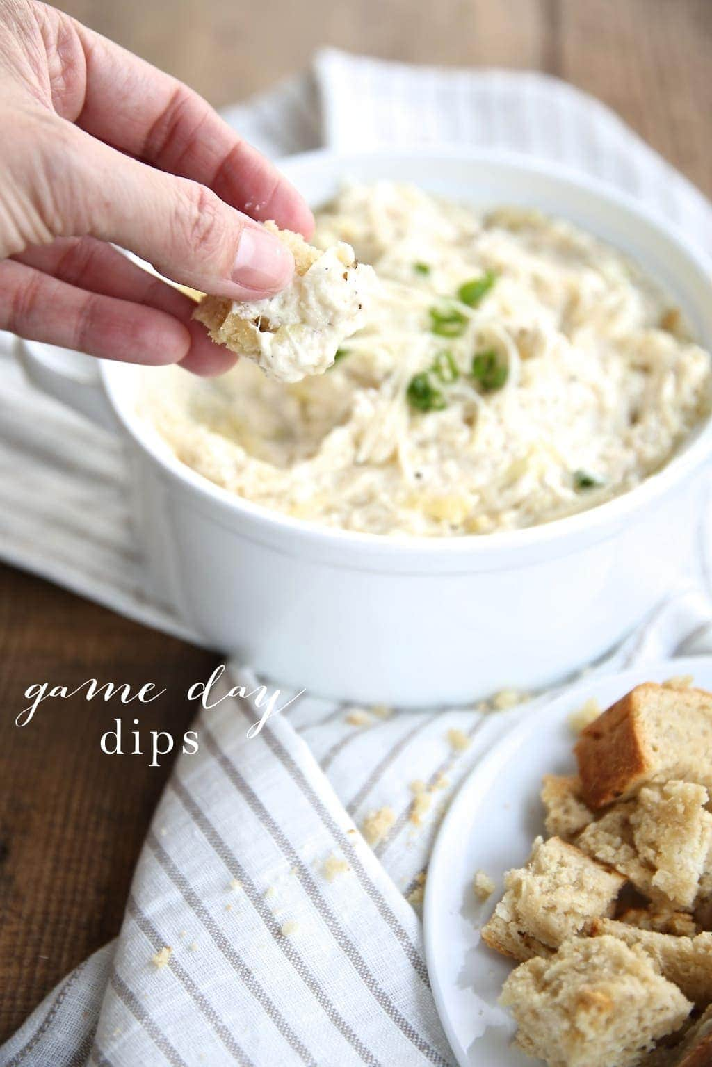 A hand dipping into a fresh easy dip recipe in a white bowl.