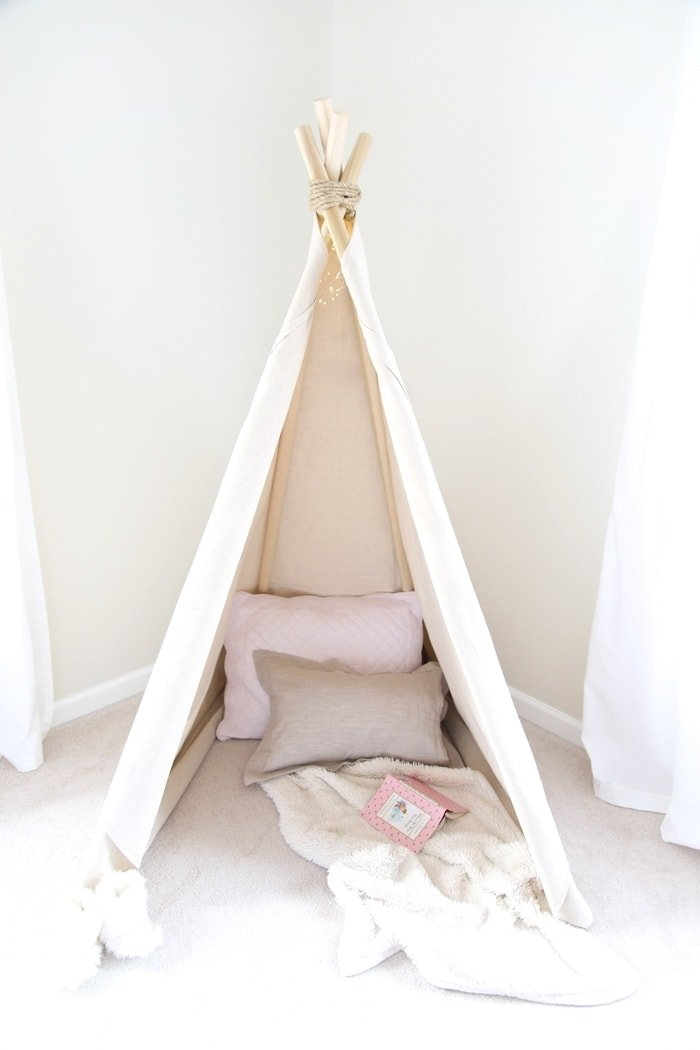 a homemade canvas teepee with pillows inside for a kids bedroom reading nook.