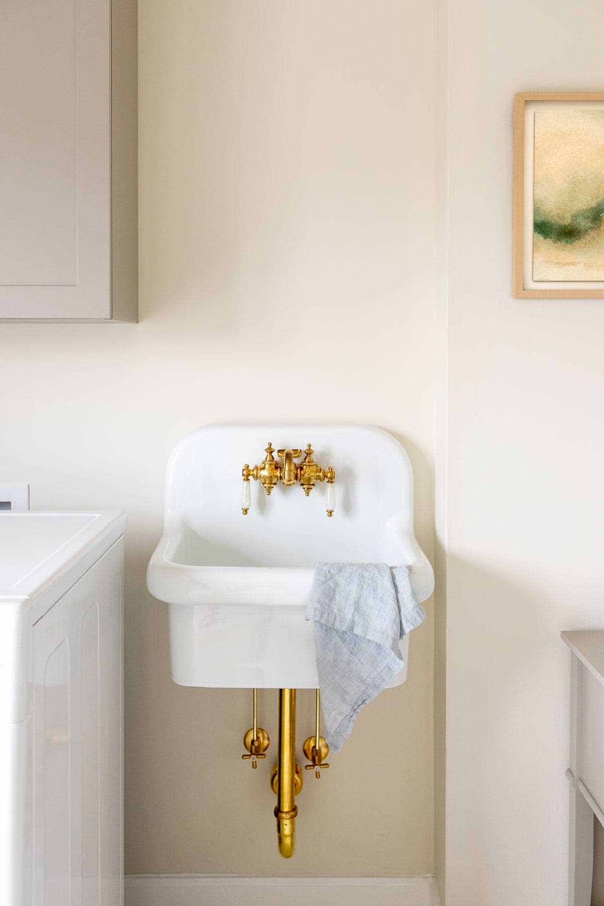 wall mount utility sink with brass pipes and faucet