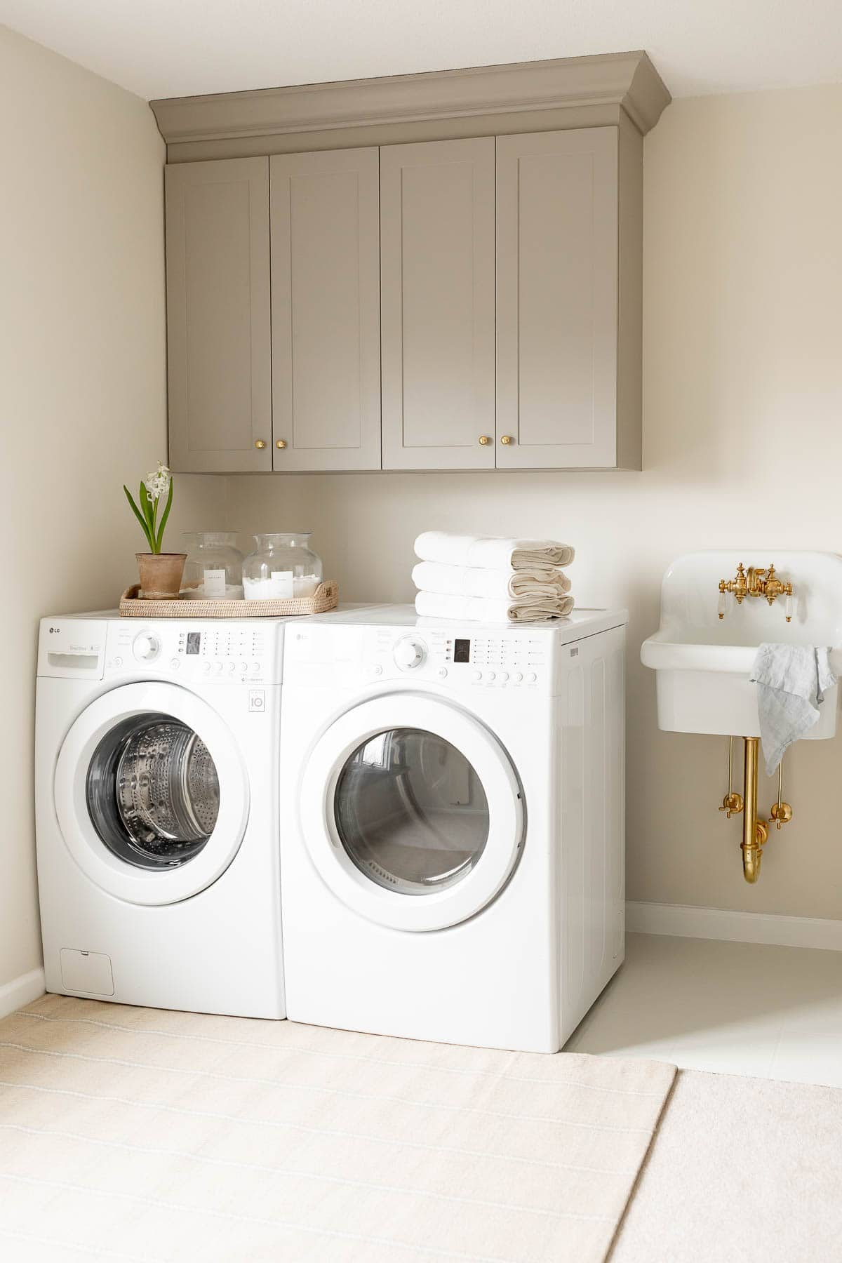 washer and dryer with laundry room wall cabinets above