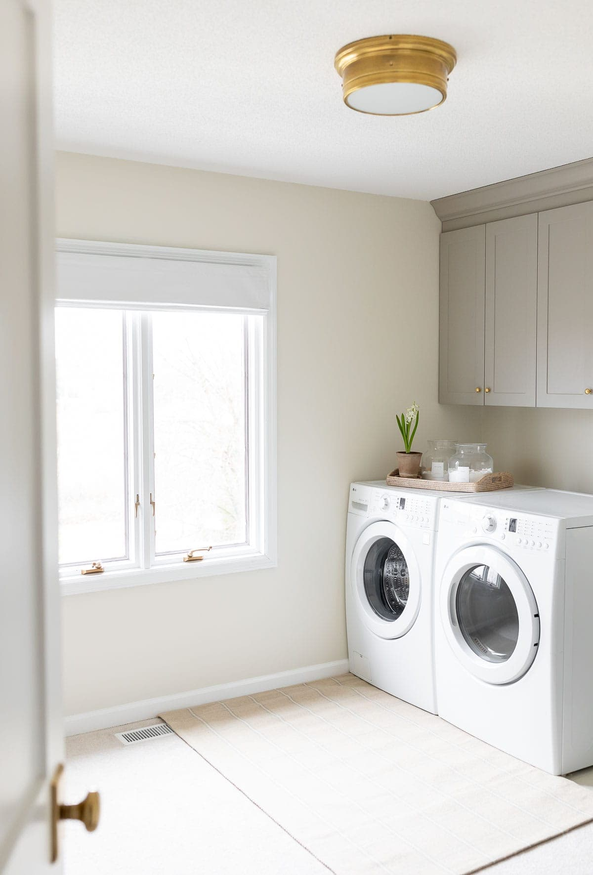 cream and gray laundry room with brass flush mount light