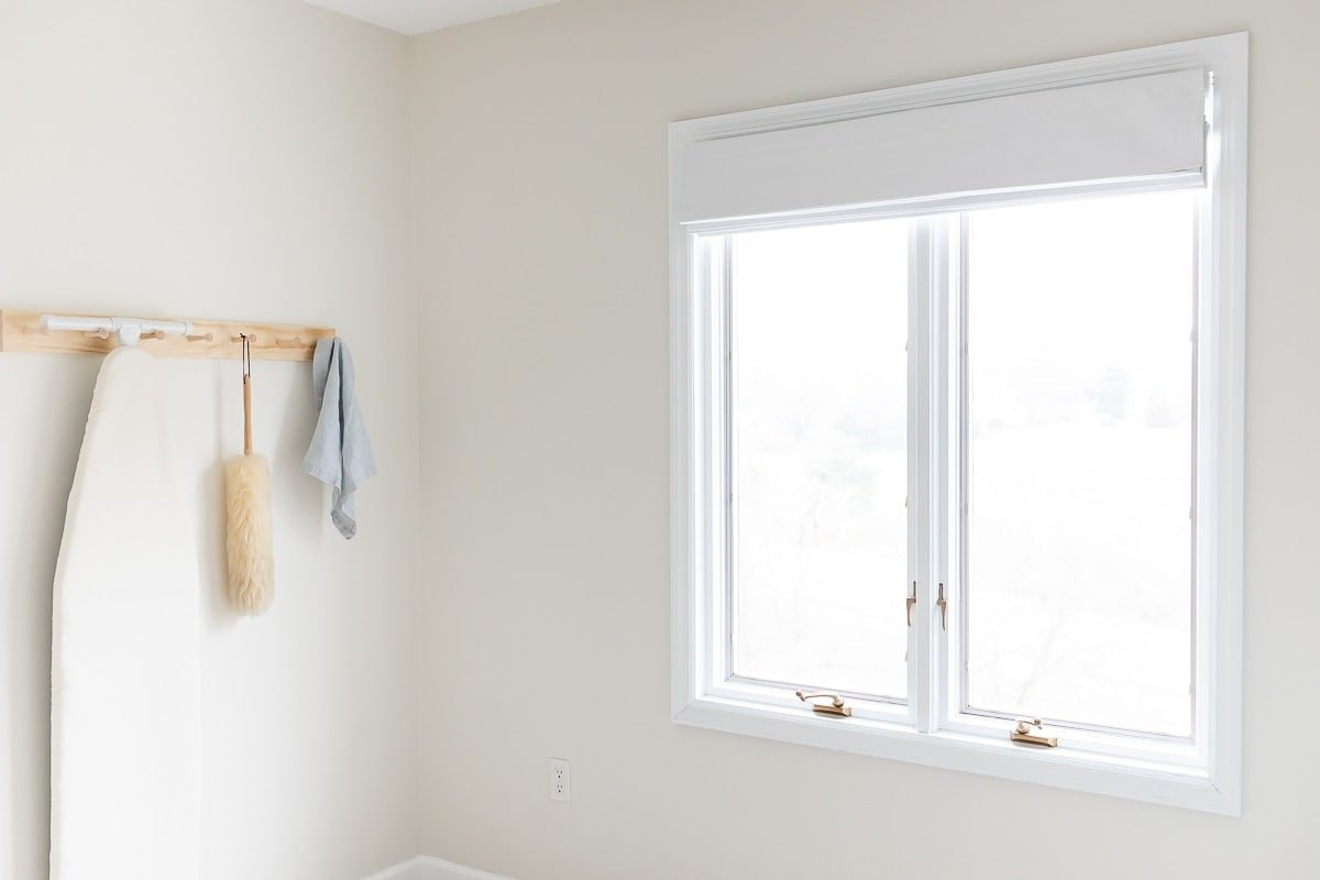 white roman shade on window next to peg rail laundry room storage