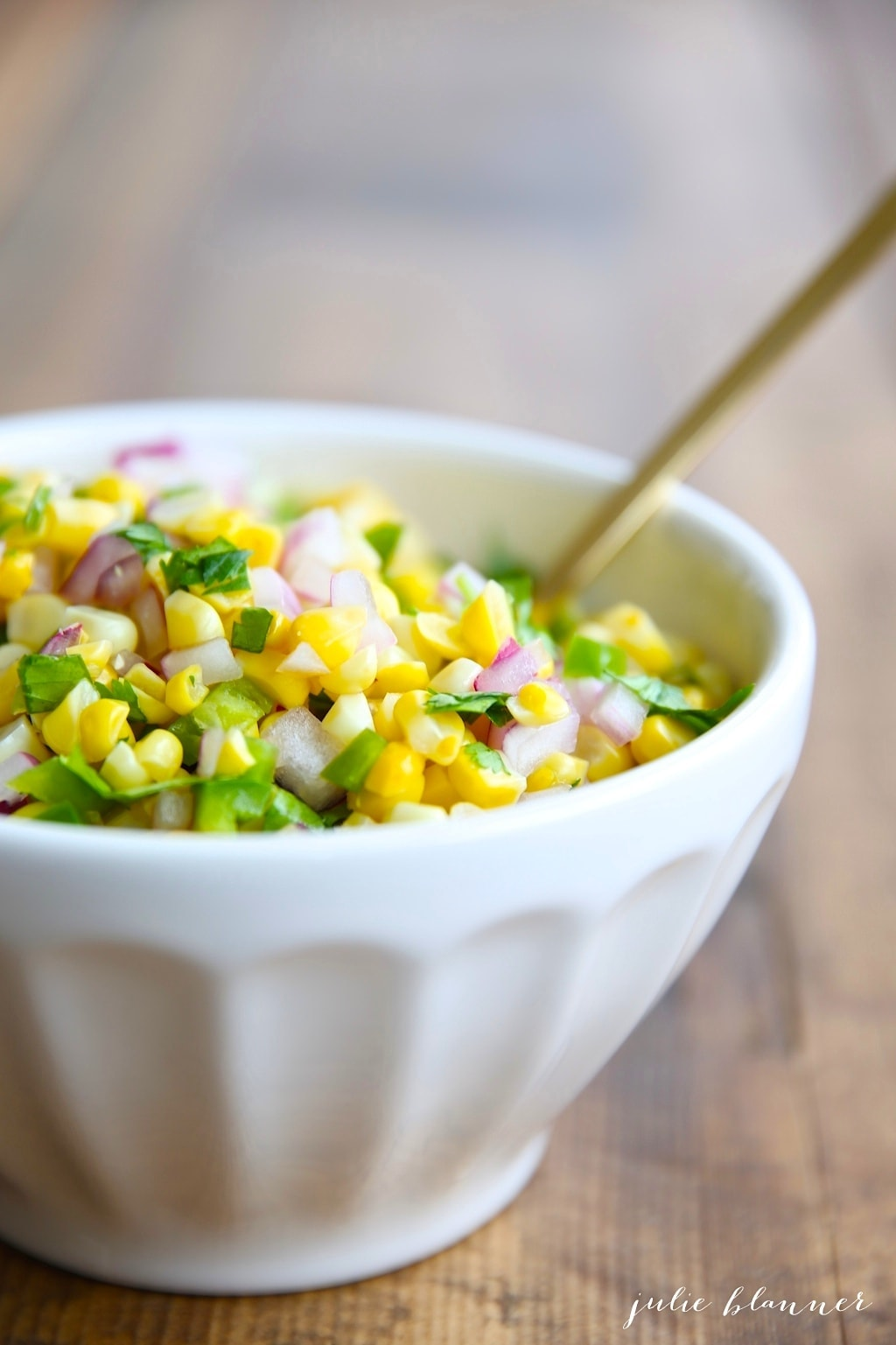 A white bowl full of chipotle corn salsa, gold spoon sticking out to the side.