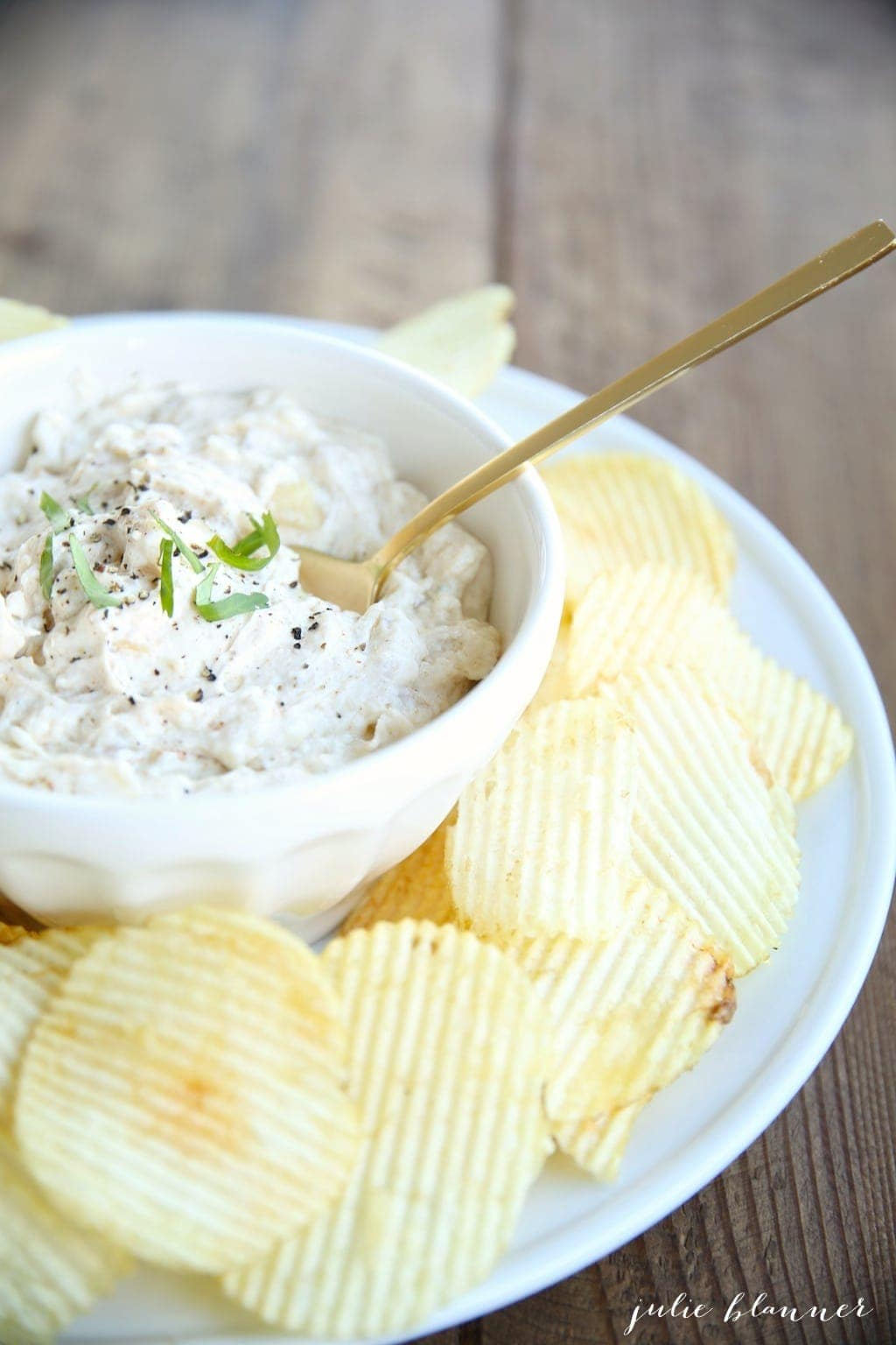 A white bowl with an easy dip recipe, gold spoon for serving.