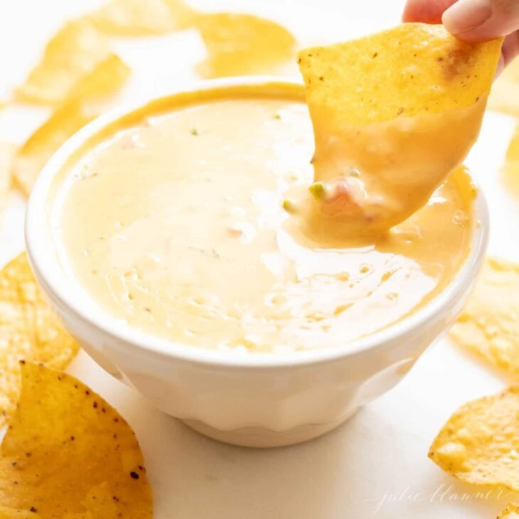 dipping a chip into a white bowl filled with velveeta cheese dip