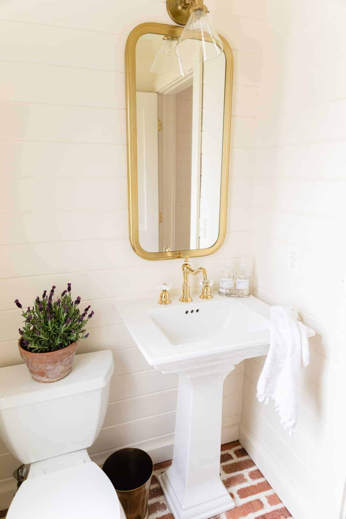 brass sconce over mirror and sink in bathroom