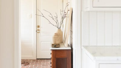brass light in mudroom with brick floors
