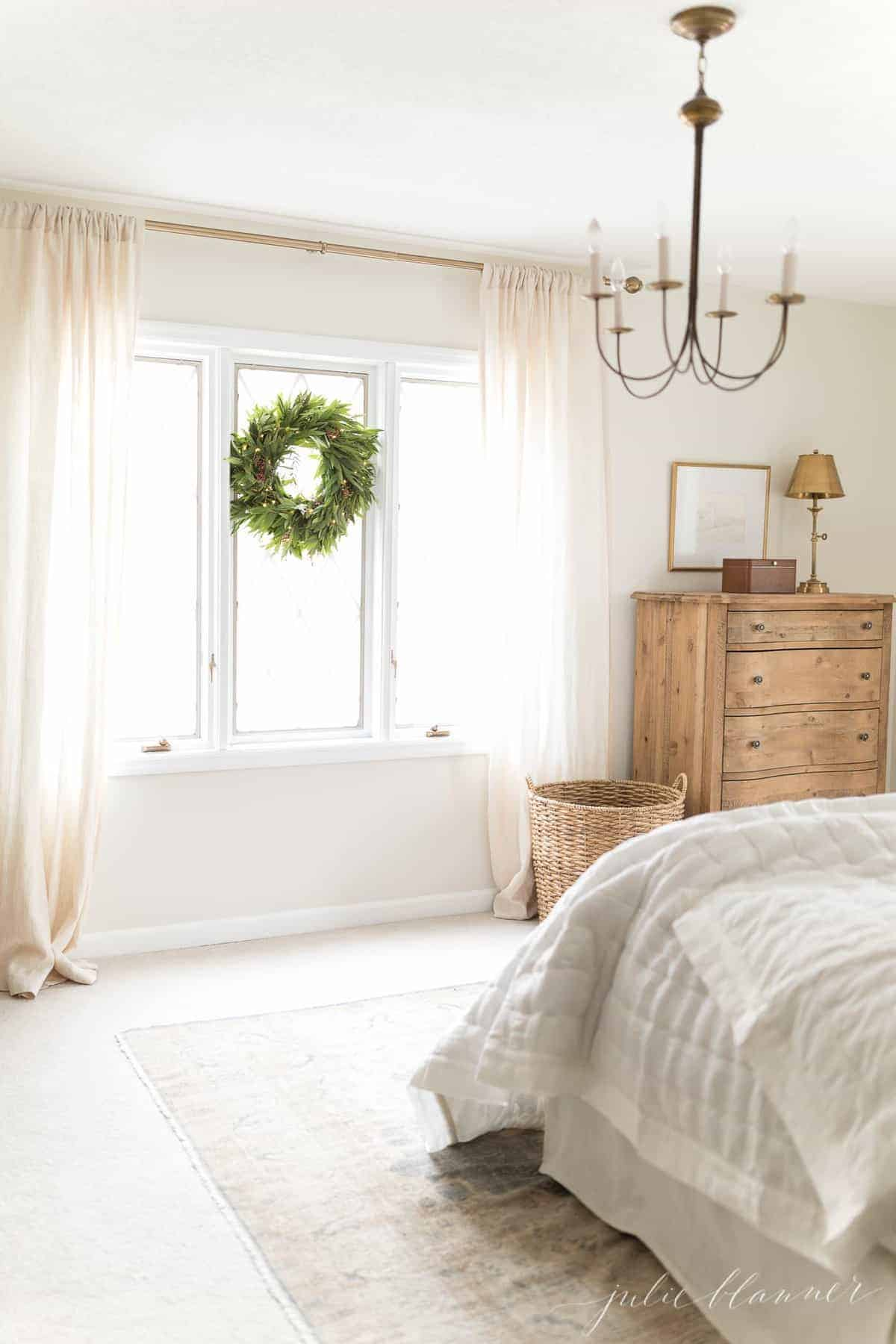 A white bedroom featuring brass lighting with a chandelier and lamp.