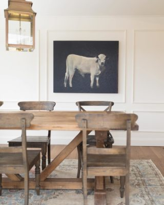 farmhouse table on vintage rug with cream colored walls large cow painting and brass lantern pendant