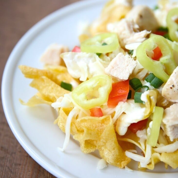 Incredible Italian nachos recipe with asiago cream sauce on a bed of pasta chips!