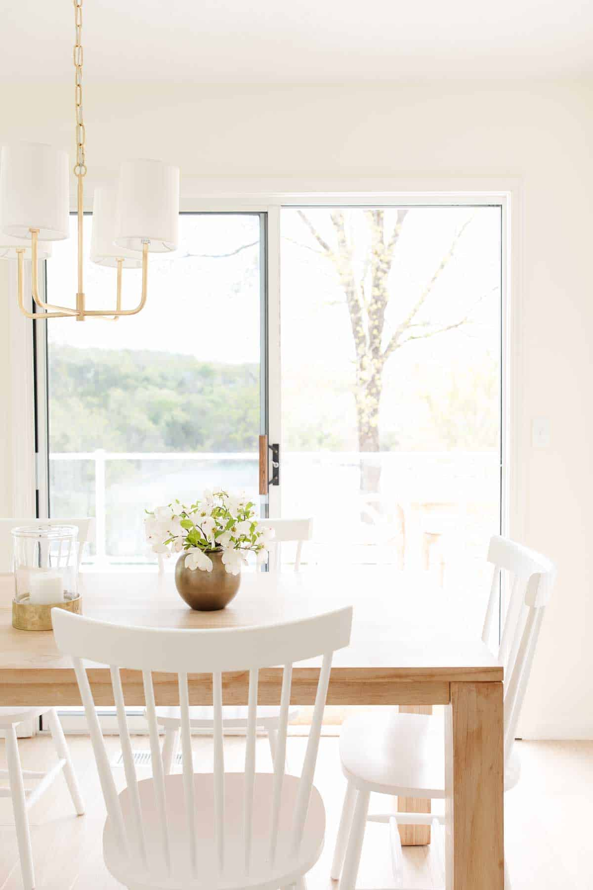 modern brass chandelier with shades over a kitchen table with flowers
